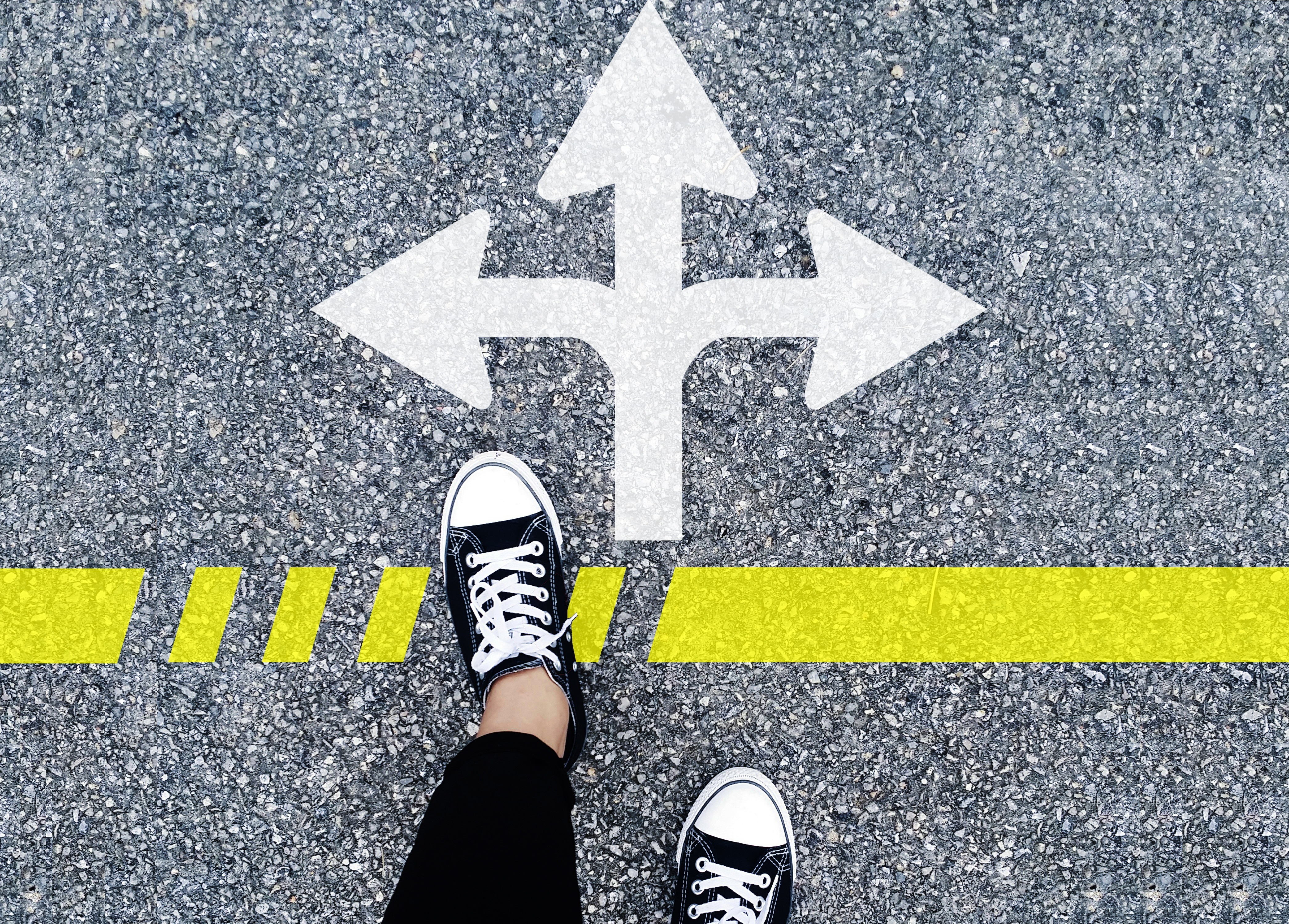 Selbstbestimmt in allen Lebenslagen - Füße einer Person vor Richtungspfeil links-geradeaus-rechts auf Straße