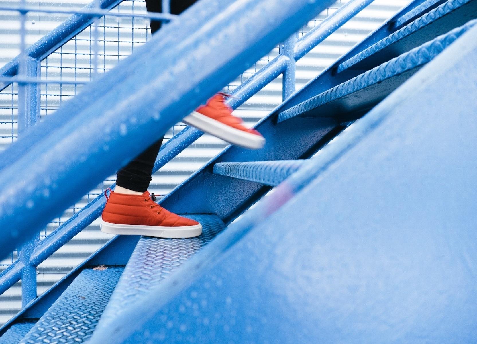 Vorankommen durch eigene Leistung - Person mit orangenen Schuhen, die zügig eine blaue Treppe hinaufsteigt