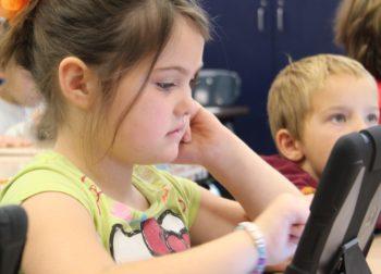 Weltbeste Bildung für jeden - Kleines Mädchen mit Tablet in Klassenzimmer